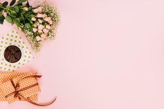 Blumen in der Nähe von Dessert und Geschenken