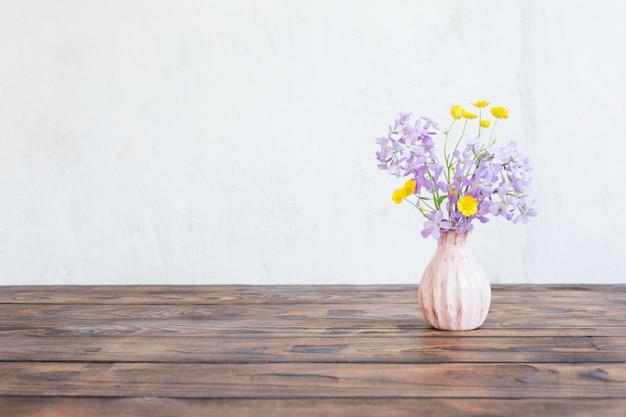 Blumen in der vase auf holztisch auf oberflächlicher weißer wand