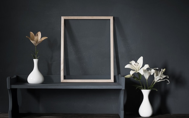 Blumen in der vase und im holzrahmen auf dunkler hintergrundwand