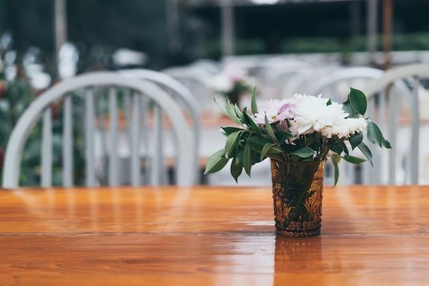 Blumen in der vasendekoration auf tabelle