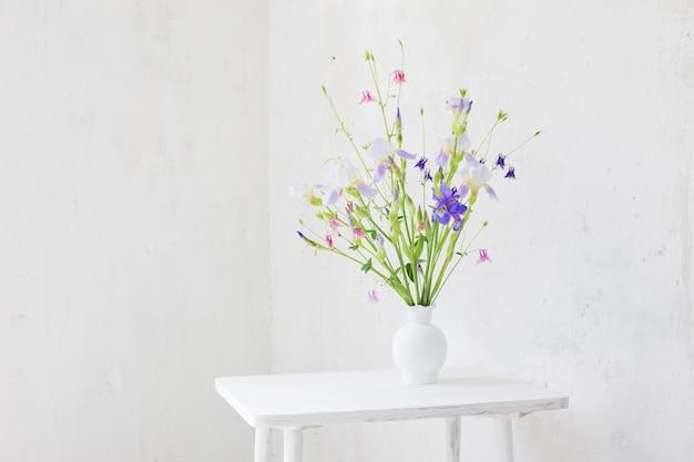 Blumen in der weißen vase im weißen vintagen innenraum