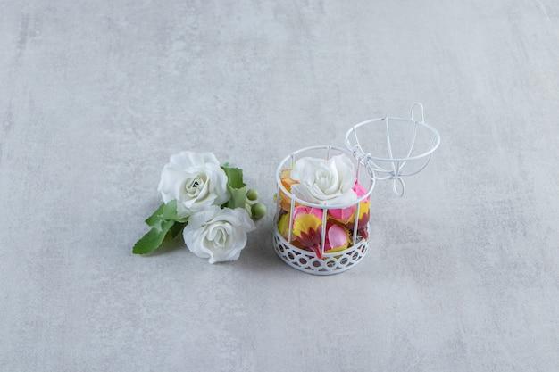 Blumen in einem käfig neben rosen auf dem weißen tisch.