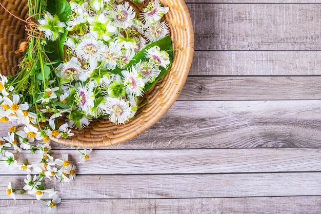 Blumen in einem korb auf einem hölzernen hintergrund