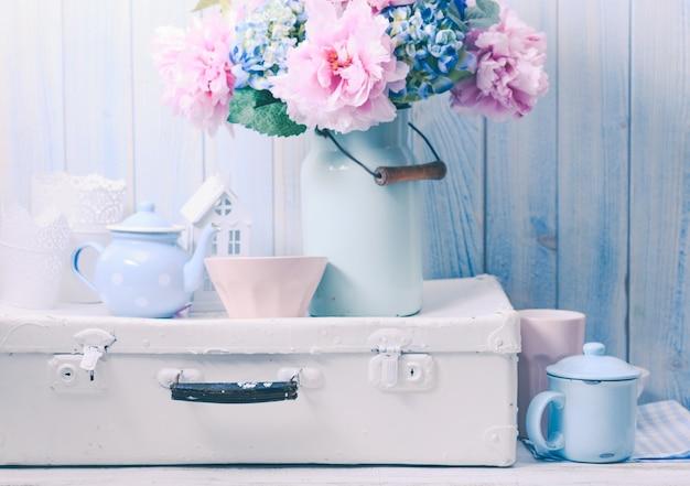 Blumen in einer blauen vintage-dose auf weißer retro-tasche und küchen-steingut