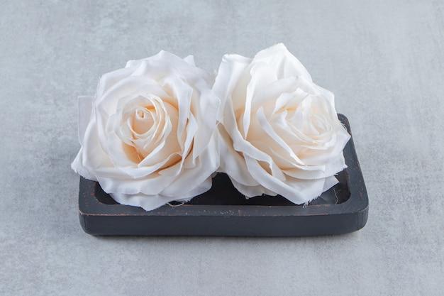 Blumen in einer holzplatte, auf weißem hintergrund.
