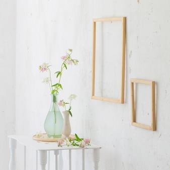 Blumen in vase und holzrahmen auf weißem innenraum