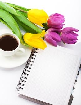 Blumen, kaffee und notizbuch.