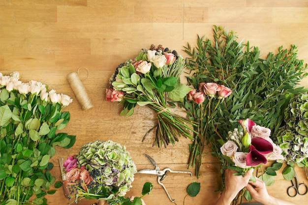 Blumen lieferung draufsicht. florist, der ordnung schafft, rosenstrauß im blumenladen macht.