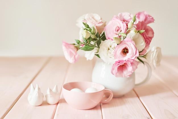 Blumen mit eiern für ostern auf rosa holz