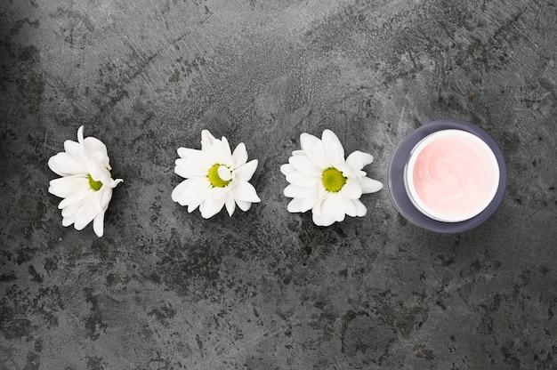 Blumen mit einem glas sahne auf einem dunklen marmorhintergrund. sicht von oben. naturkosmetik.