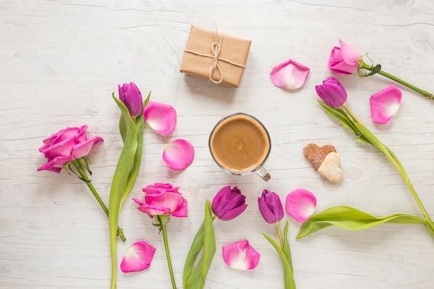 Blumen mit geschenkbox und kaffee auf dem tisch