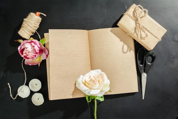 Blumen mit leerem weinlesenotizbuch
