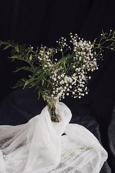 Blumen mit pflanzen in der vase in der nähe von weißen textilien und perlen