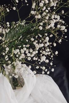 Blumen mit pflanzen in der vase in der nähe von weißen textilien