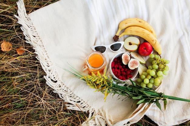 Blumen mit picknickfrüchten im park. glas mit saft und frauengläsern und mittagessen im freien