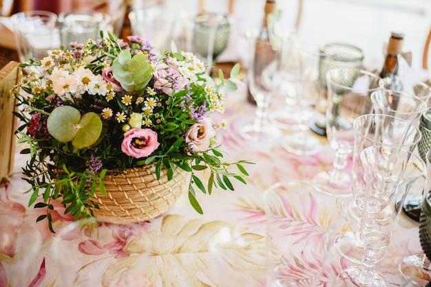 Blumen schmücken die mittelstücke mit luxusbesteck auf den tischen einer hochzeitshalle.