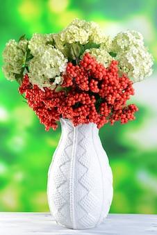 Blumen und beeren in vase, auf holztisch, auf hellem hintergrund