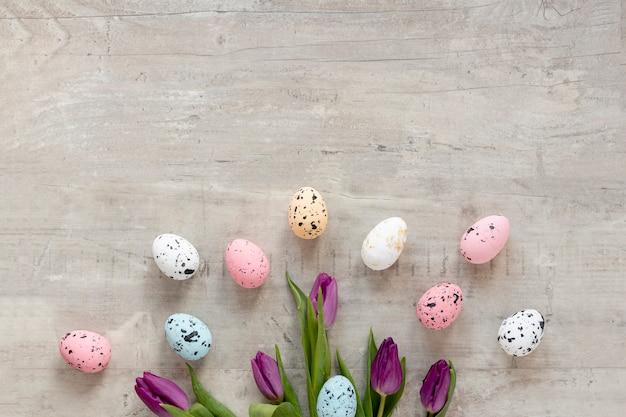 Blumen und bemalte eier auf dem tisch