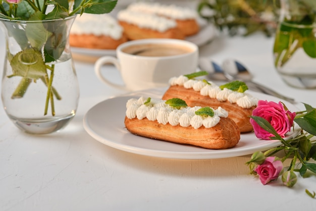 Blumen und eclairs dekoriert mit creme und minze auf einem weißen tisch. dessert für ein romantisches date. kuchen für den urlaub.