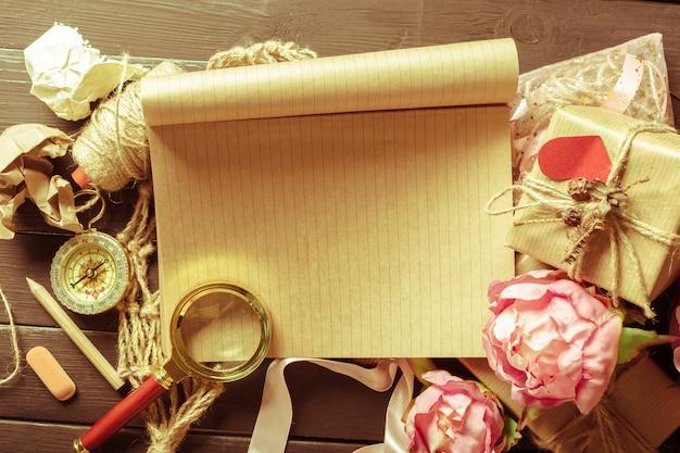 Blumen und ein notizbuch auf hölzernem