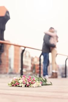 Blumen und ein umarmtes paar im hintergrund