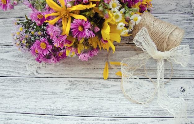 Blumen und eine garnrolle auf einem hölzernen hintergrund