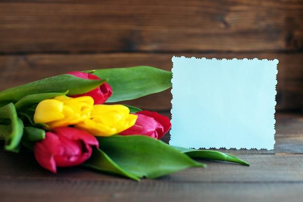Blumen und eine willkommenskarte auf dunklem hölzernem hintergrund.
