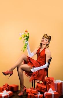 Blumen und geschenk glückliches mädchen mit geschenkbouquet von tulpen retro-frau mit geschenkbox und blumen