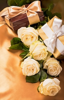 Blumen und geschenk. weiße rosen auf goldenem seidenhintergrund