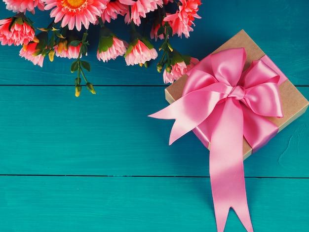 Blumen und geschenkbox auf hölzerner rustikaler tabelle. mutter oder valentinstag grußkarte. kopieren sie platz für text.