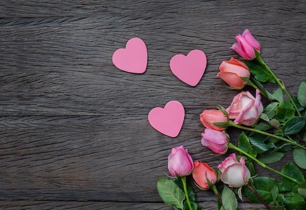 Blumen und herzen auf einem hölzernen hintergrund. rosen und platzende herzen auf einer dunklen holzoberfläche