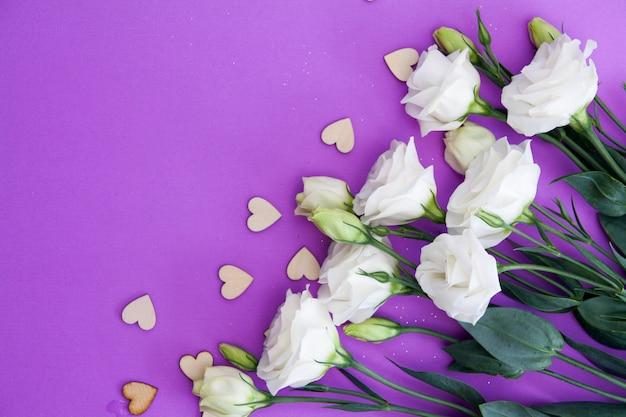 Blumen und herzen auf einem lila hintergrund. . für glückwünsche leer.
