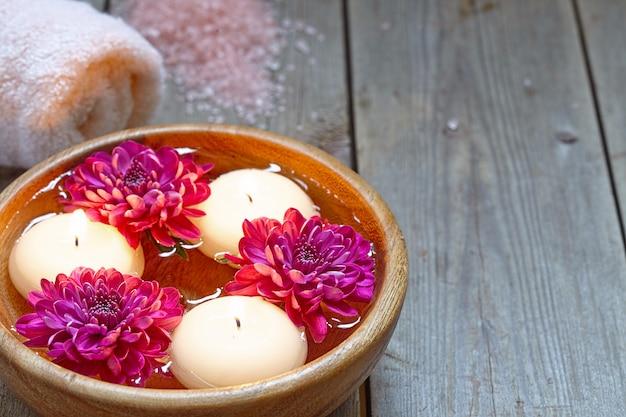 Blumen und kerzen in schüssel mit wasser