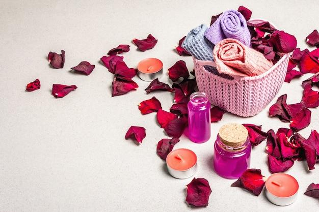 Blumen- und spa-konzept mit getrockneten rosenblättern, duftenden kerzen und weichem handtuch