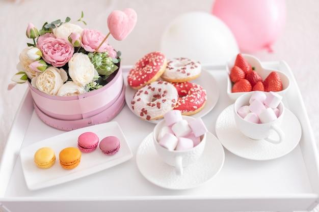 Blumen und süßigkeiten auf weißem tisch und luftballons auf dem weißen bett. geschenk zum muttertag Premium Fotos