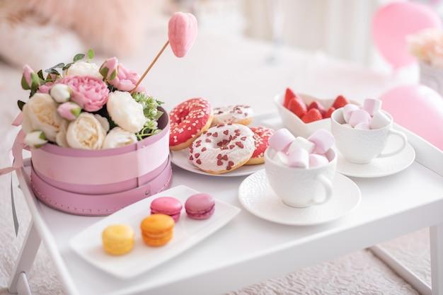 Blumen und süßigkeiten auf weißem tisch und luftballons auf dem weißen bett. geschenk zum muttertag