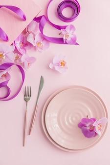 Blumen- und tabelleneinstellungen über kopfzusammensetzung auf hellrosa hintergrund. rosa keramikteller, besteck, rosa geschenktüte mit lila bändern und rosa orchideenblüten