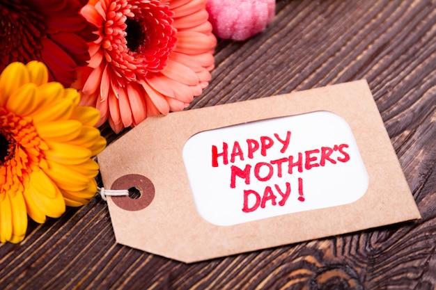 Blumen und tag der mutter. gerbera in der nähe von süßigkeiten und etikett. sei großzügig mit mama. geste der liebe und des respekts.