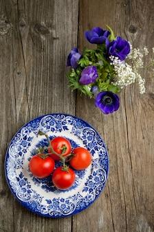 Blumen und teller mit frischen tomaten