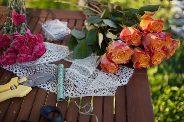 Blumen und werkzeuge auf dem tisch, floristenarbeitsplatz, stillleben