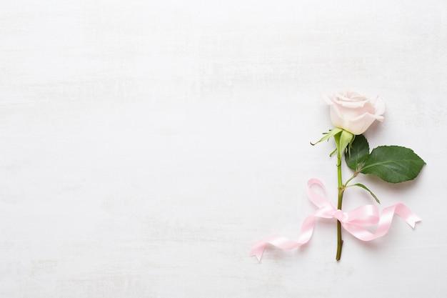 Blumen valentinstag grußkarte. rahmen aus rosa rose auf grau.