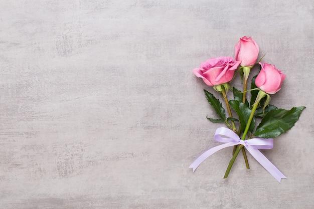 Blumen valentinstag zusammensetzung. rahmen aus rosa rose auf grau. flache lage, draufsicht, kopierraum.