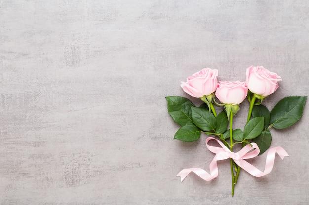 Blumen valentinstag zusammensetzung. rosa rose auf grauem hintergrund. flache lage, draufsicht.