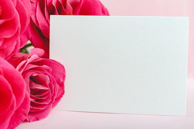 Blumen verspotten glückwünsche. glückwunschkarte im blumenstrauß aus rosa roten rosen auf rosa hintergrund. weiße leere karte mit platz für text, rahmenmodell. frühlingsfestliches blumenkonzept, geschenkkarte.