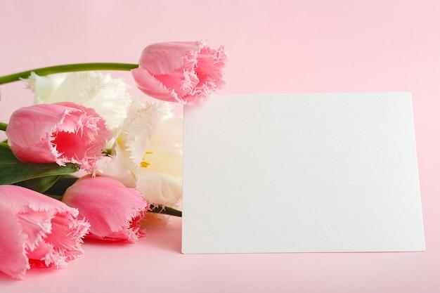 Blumen verspotten glückwünsche. glückwunschkarte im strauß rosa tulpen auf rosa hintergrund. weiße leere karte mit platz für text, rahmenmodell. frühlingsfestliches blumenkonzept, geschenkkarte.