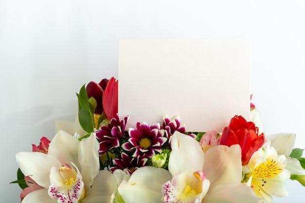 Blumen verspotten glückwünsche leere leere karte im blumenstrauß auf weißem sommerhintergrund