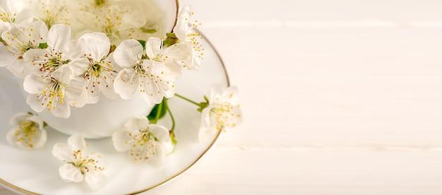 Blumen von einem apfelbaum in einer weißen porzellantasse