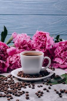 Blumen von pfingstrosen mit rosa knospen und kaffee in einer tasse