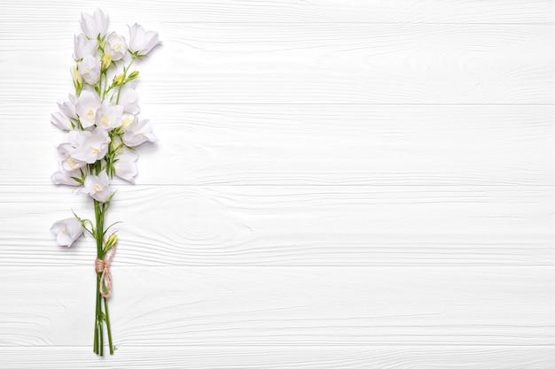 Blumen weiße glocken auf einem weißen hölzernen hintergrund.