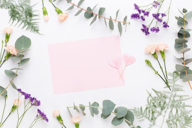 Blumen zusammensetzung. papierrohling, nelkenblumen, eukalyptuszweige auf pastellhintergrund. flache lage, draufsicht, kopierraum